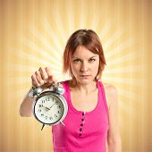 Serious Redhead Girl Holding A Clock Over Pop Background