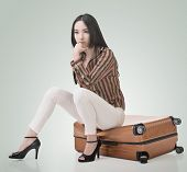 Asian woman thinking and sitting on a luggage, full length portrait isolated on white background.