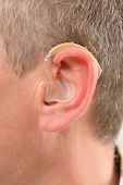 foto of deaf  - Man showing deaf aid in ear - JPG