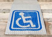 stock photo of disable  - The blue sign indicating on wheelchair usage on steel ramp for disabled people - JPG