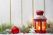 Christmas ball,lantern and fir branch on wood plank.
