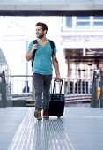 Cheerful Man Walking With Bags At Train Station