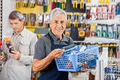 Portrait of smiling senior salesman holding tools basket with customer in background at hardware sto