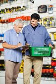 Father and son with checklist buying tools in hardware store