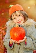 Autumn girl wearing orange hat and holding pumpkin in hands. Warm sunlight background.