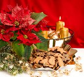 image of poinsettia  - festive advent decoration with burning golden candles poinsettia flower and christmas gingerbread cookies - JPG