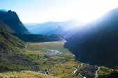 Dawn in Val Veny, with sunlight breaking through mountains and falling on Combal Lake. The region is