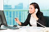 Asian Chinese business woman telephoning in office controlling profit