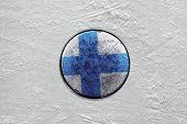 Finnish puck on the ice hockey rink. Closeup