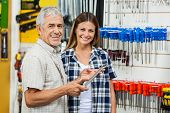 Portrait of happy senior man and daughter with wrench in hardware shop