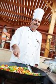 Arab chef in cook uniform frying meat with vegetables on pan outdoors
