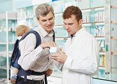 pharmaceutical chemist male worker consulting young father with child in pharmacy drugstore