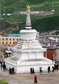 Monks And Tibetan People Walking Around White Stupa