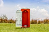 Standalone Of Red Toilet With White Door Open Contrast With Green Grass And Tree In The Meadow.