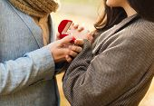 love, relationship, family and people concept - close up of couple with red gift box in autumn park