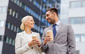 business, partnership, hot drinks and people concept - smiling businessmen with paper cups standing