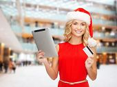 christmas, technology, shopping and people concept - smiling woman in santa helper hat with tablet p