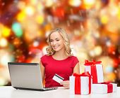christmas, holidays, technology and shopping concept - smiling woman in red blank shirt with gift bo