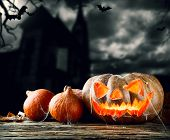 Concept of halloween pumpkins on wooden planks. Blur scary church on background