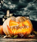 Concept of halloween pumpkin on wooden planks. Blur scary castle on background