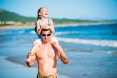 Portrait of happy father and his smiling little daughter on the beach