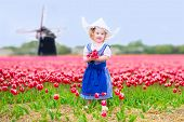 Adorable curly toddler girl in Dutch costume field of tulips