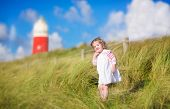Cute Toddler Girl Next To A Red Lightshouse On A Beach