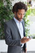Handsome businessman texting on phone on a sunny day