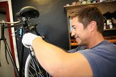 Cheerful man working in bicycle workshop