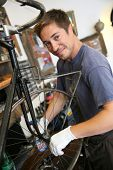 Man in bike workshop fixing back wheel