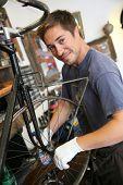 Man in bike workshop fixing back wheel