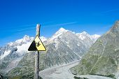 COMBAL, ITALY, AUGUST 28: Slippage danger sign with Miage Glacier and Combal peaks in the background