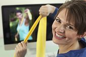 stock photo of workout-women  - Attractive young woman pulls on resistance bands while smiling back at the camera - JPG