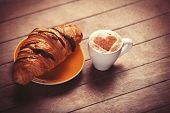 image of crescent-shaped  - french croissant and cup of coffee on a wooden table - JPG