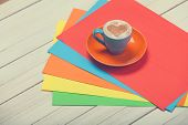 Cup Of Coffee And Color Paper On Wooden Table.