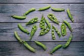 Pods Of Fresh Green Peas On Wooden Table