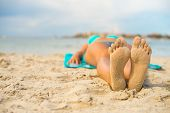 Woman Sunbathing On Sand. Place For Text.
