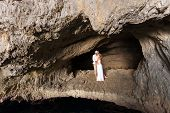 stock photo of cave woman  - portrait of a young couple in love inside a cave of a greek island - JPG