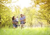 image of father time  - Happy young family spending time together outside in green nature - JPG
