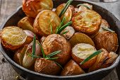 pic of baked potato  - baked potatoes in a pan with rosemary