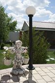 stock photo of yoke  - Garden figurine girl with a yoke near the lamp - JPG