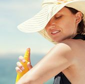 stock photo of sun tan lotion  - Woman applies suntan lotion during sunny day on the beach - JPG