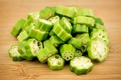 pic of okras  - Pile of sliced okra bhindi pieces on rustic wooden background - JPG