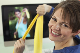 foto of workout-women  - Attractive young woman pulls on resistance bands while smiling back at the camera - JPG