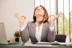 stock photo of breathing exercise  - Stressed young business woman doing some breathing exercises and meditating at her office - JPG