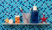 stock photo of personal hygiene  - Personal hygiene products on bathroom shelve on blue background - JPG