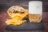 image of potato chips  - Beer with foam in glass mug and potato chips in bag on wooden table  - JPG
