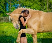 image of horse girl  - A girl is hugging a palomino horse  - JPG