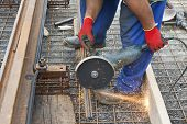 pic of millwright  - man holding grinder cutting metal near a railway - JPG