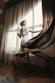 picture of curtain  - The woman straightens out the window the curtain - JPG